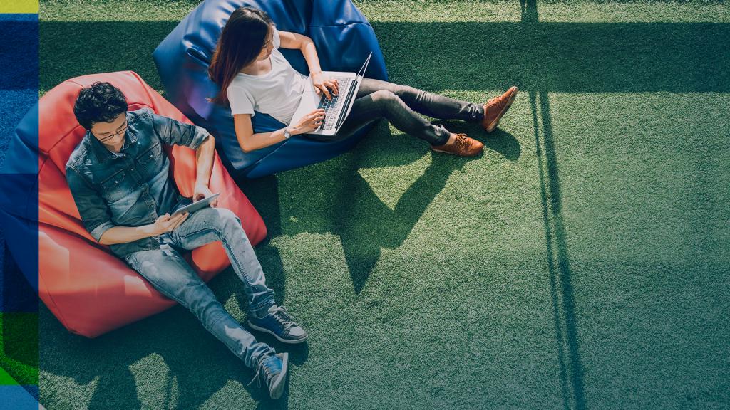 Jovens com jornada de trabalho flexível sentados em pufes no gramado.