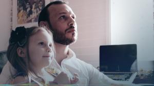 Fernando e sua filha assistindo ao vídeo de canções infantis.