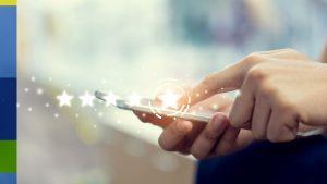 Foto das mãos de uma pessoa usando um smartphone. Em cima da foto, está a imagem de quatro estrelas.
