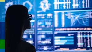 Foto de uma mulher de óculos olhando para uma tela grande e cheia de números e dados.