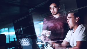 Foto de dois homens em frente a um computador, conversando e apontando para a tela.
