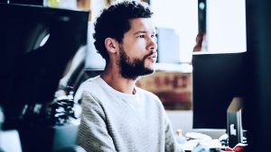 Foto de homem concentrado, usando um computador.