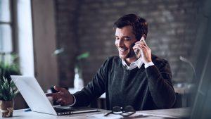 Foto de homem demeia idade falando ao telefone enquanto está em frente a um note book.