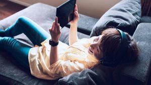 Foto de mulher olhando para um tablet e usando fones de ouvido.