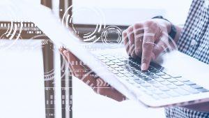 Foto das mãos de uma pessoa utilizando um notebook, com alguns grafismos que passam a ideia de tecnologia.