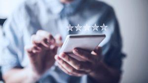 Foto de pessoa usando um celular. E cima do celular, estão 5 estrelas, representando como fidelizar clientes.
