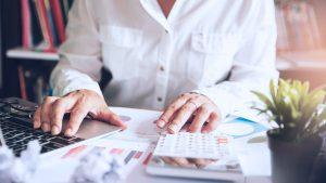 Foto de uma pessoa usando uma calculadora e um notebook, em meio a papeis.