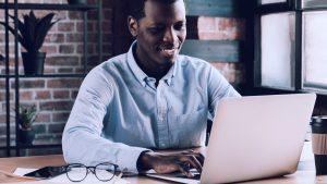 Foto de homem trabalhando junto a um notebook, em casa.