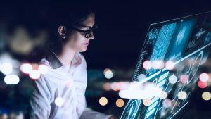 Foto de uma mulher interagindo com uma tela com informações e dados digitais.