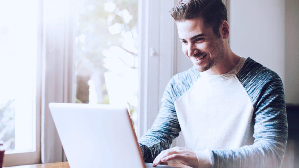 Foto de homem com expressão feliz enquanto usa um notebook em casa.