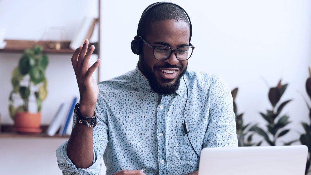 Foto de um homem usando fones de ouvido e um notebook, conversando por videoconferência.