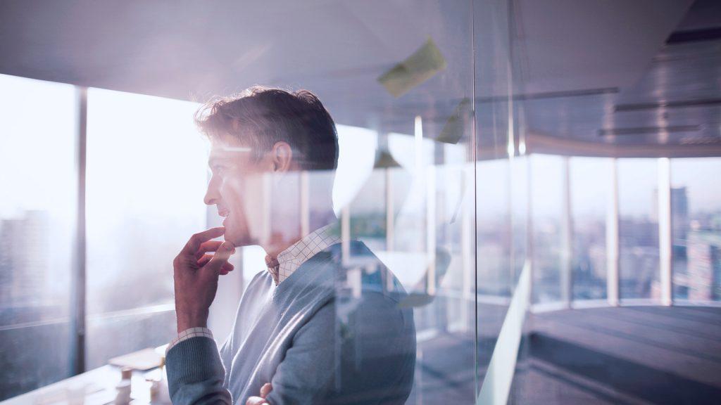 Foto de homem olhando para a janela enquanto pensa na nova realidade.