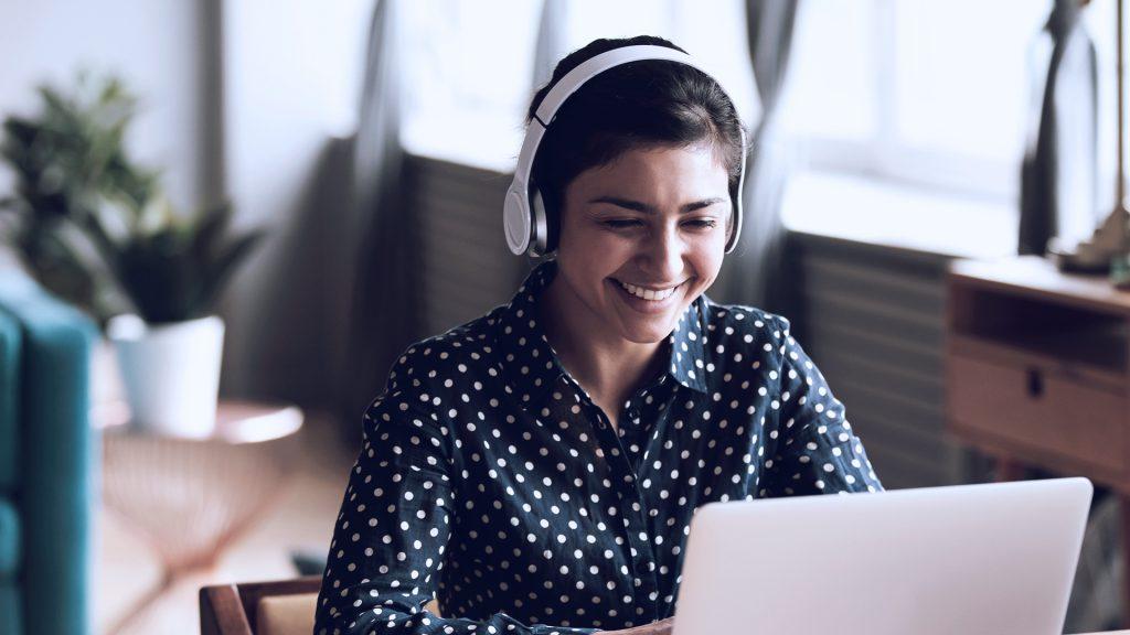 Foto de mulher sorrindo enquanto usa o computador e fones de ouvido.