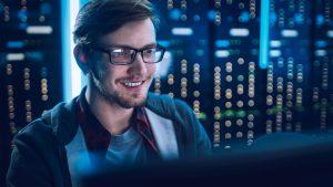 Foto de homem em frente a um computador, fazendo a gestão de metadados.