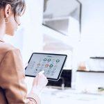 Foto de uma mulher usando um tablet para controlar ações relacionadas a Internet das Coisas em casa.