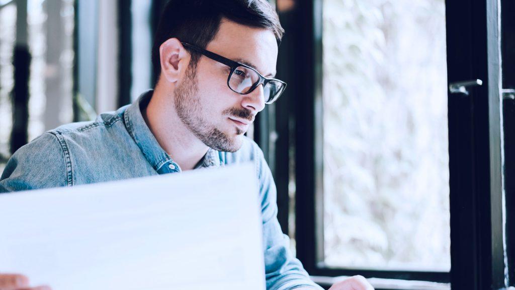 Foto de homem analisando papeis e modelos de negócio.