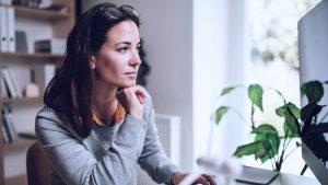 Mulher olhando para uma tela de computador, pensando sobre a sustentabilidade empresarial.