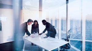 imagem com dois homens e uma mulher analisando estratégias em uma mesa