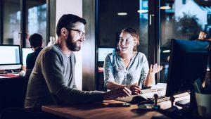 Foto de duas pessoas conversando no trabalho, representando as soft skills e hard skills.