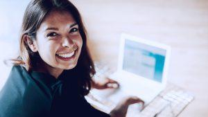 imagem com mulher mechendo em computador, representando uma solução de marketing de afiliados