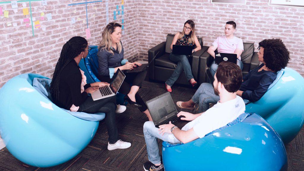 imagem com pessoas sentadas com computadores na mão que representam uma solução de inovação aberta