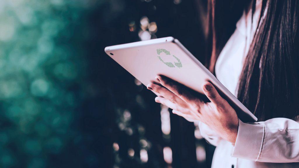 imagem de uma mulher com tablet na mão que representa uma solução de sustentabilidade empresarial